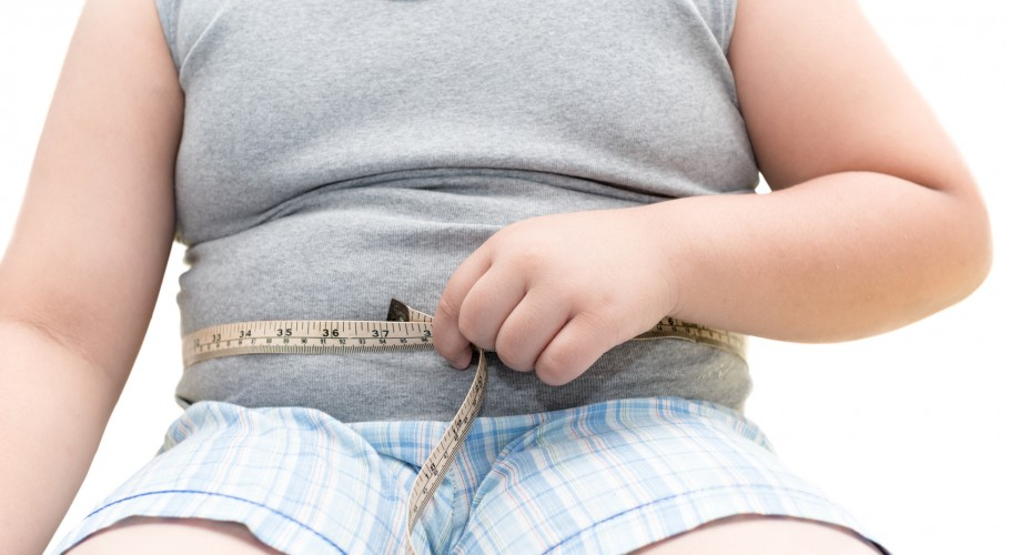 Obese fat boy measuring his belly with measurement tape, unhealthy concept